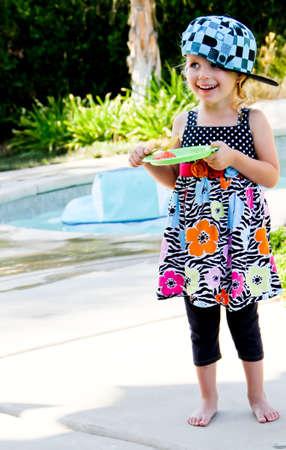 female toddler eating watermelon near swimming pool Stock Photo