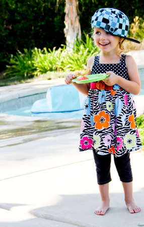 female toddler eating watermelon near swimming pool Standard-Bild