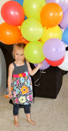 laughing female toddler with a bunch of colored balloons