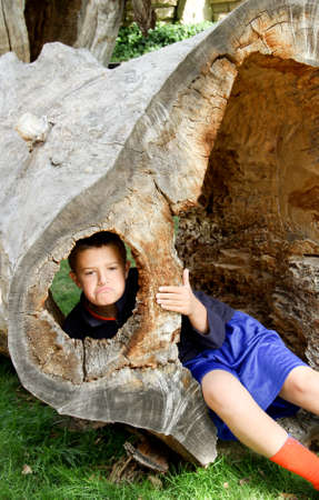 preteen boy looking out of hole in hollow tree