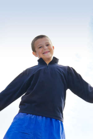 smiling preteen boy with orange braces against blue sky