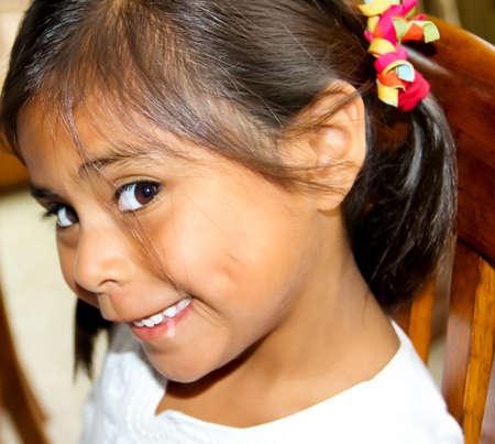 coy looking hispanic female child with long hair 版權商用圖片