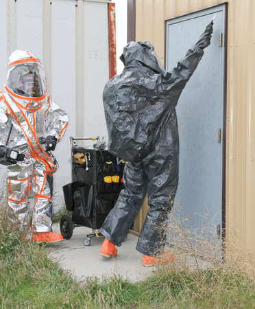 hazmat: fully suited hazmat team checking for chemical hazmat leaks on site door Stock Photo