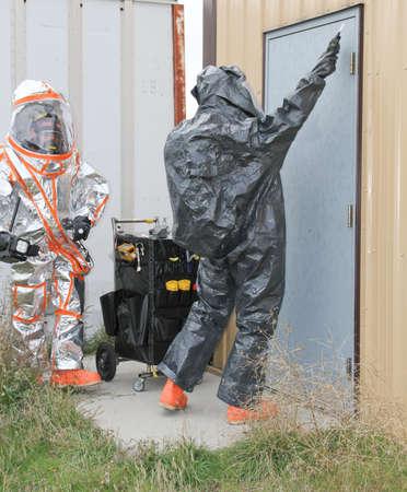 hazmat: fully suited hazmat team checking for chemical hazmat leaks on site door Stock Photo