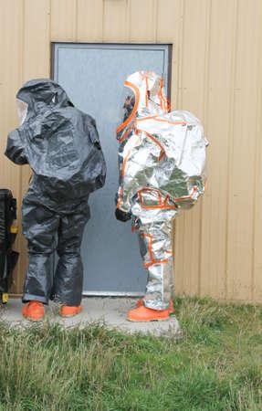 fully protected hazmat team entering smoking building