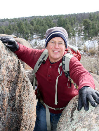 happy senior male climbing through boulders without rope