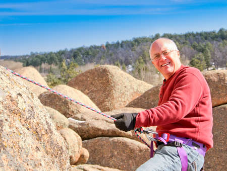 Happy Senior male climbing rocks with rope