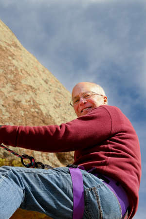 Happy, healthy Senior male rappelling on rope from rocky cliff photo