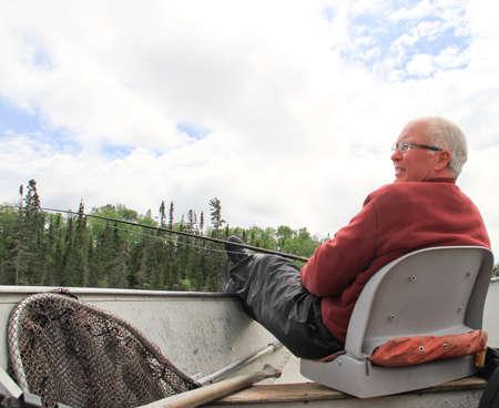 Retired alten männlichen Fischer mit Pol und Netto entspannenden im Boot Standard-Bild - 30632341