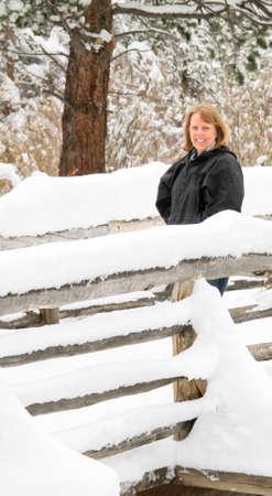Senior female on snowy footbridge