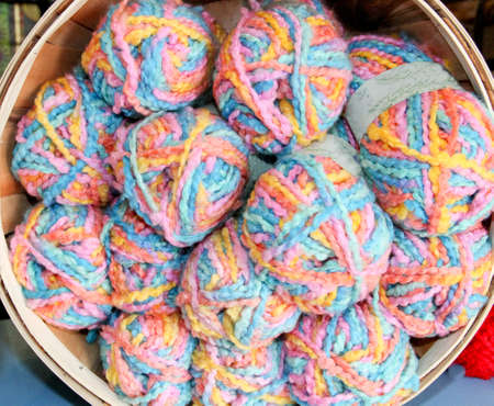 softly colored variegated baby blanket yarn in a round basket to use as background   Stock Photo