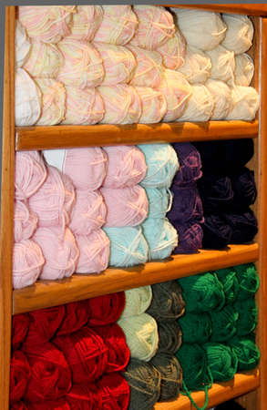 brightly colored yarn stacked in wooden display bins  Use as background Stock Photo