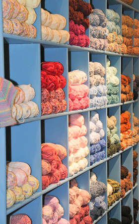 brightly colored yarn stacked in wooden display bins  Use as background Standard-Bild