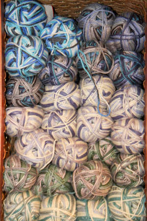 soft colored variegated yarn skeins stacked in dark basket for sale - use as background