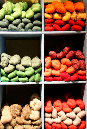 Earth tone yarn skeins stacked in bins for sale - use as background Stock Photo