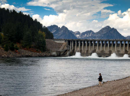 fly fisherman on bank of river near dam with Grand Tetons in background