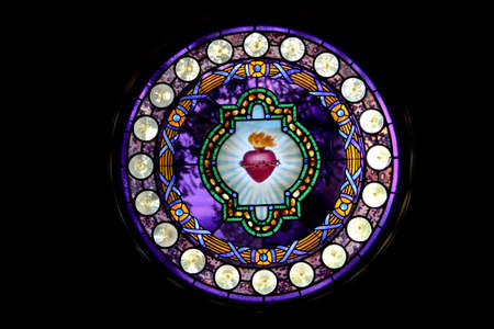 Round stained glass window picturing  Sacred Heart of Jesus with black background Stock Photo