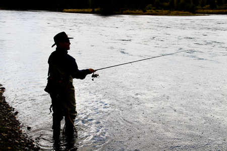 black shadow image of fly fisherman on tranquil river