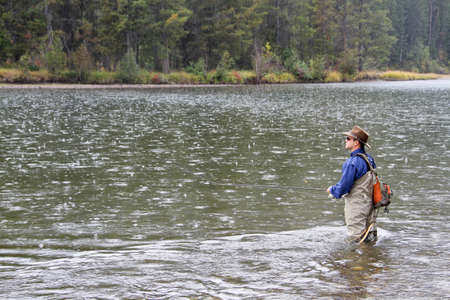 Fly fisherman standing in middle of reflective rain pocked water river