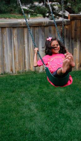 cute, smiling Hispanic female on backyard swing