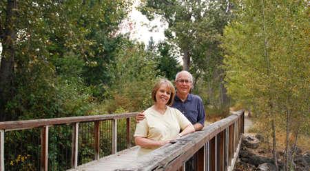 Smiling, happy senior couple resting on rural wooden bridge
