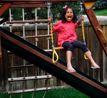 happy, screaming, Hispanic, female, child, sitting, on playground, swing, Standard-Bild