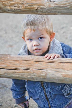 Male toddler in western denim jacket peeking through rural pole fence