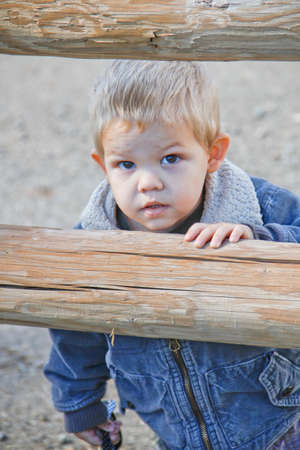 Male toddler in western denim jacket peeking through rural pole fence 版權商用圖片 - 32906127