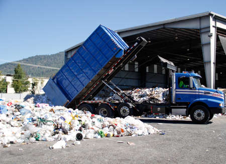 blue truck dumping paper and plastic recyclables to be hand sorted in transfer station. Editorial