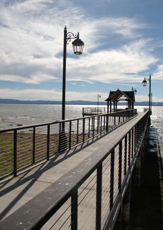 scenic pacific ocean pier with vintage lamppost and cloudy blue sky Standard-Bild