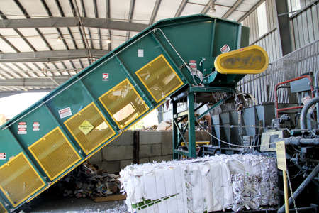Industrial sized automatic paper baler with baled office paper Editorial
