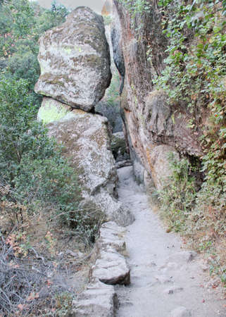 hiking trail passing under leaning boulder overhang Stock Photo