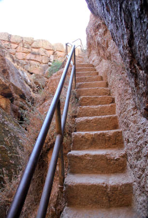 red stone stairway steps carved into solid rock cliff face
