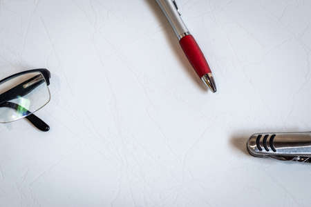 pen, glasses and pocket knife isolated in the corners on white background Foto de archivo