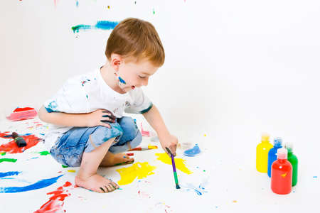 Three year old boy painting the floor and making a big mess photo