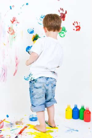 pintura infantil: Ni�o de tres a�os de edad, haciendo la mano pintada en la pared Foto de archivo