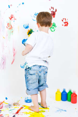 Three year old boy making painted hand prints on the wall