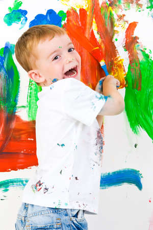paintings: Three year old boy having a lot of fun painting a wall