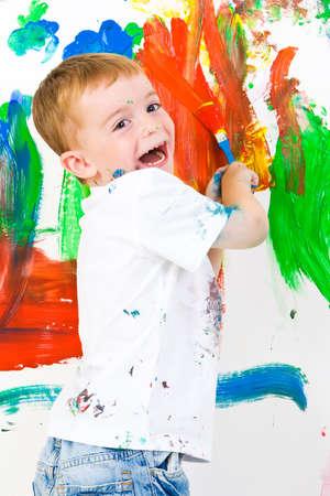 ni�os pintando: Tres a�os de edad con un chico muy divertido pintar un muro