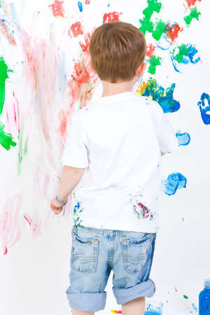 reviewing: Three year old boy reviewing his wall painting Stock Photo