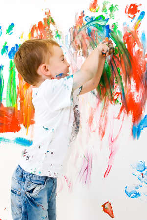 Three year old boy having a lot of fun painting a wall photo