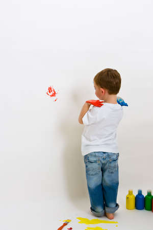 Three year old boy making hand prints on the wall Stock Photo