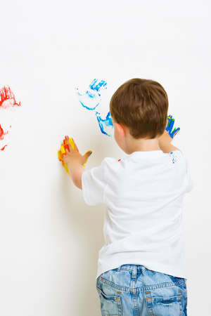 Three year old boy making painted hand prints on the wall photo