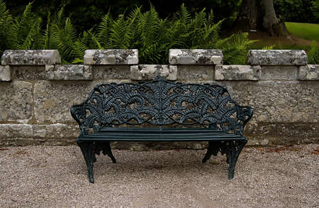 A large black cast iron garden benche to sit on