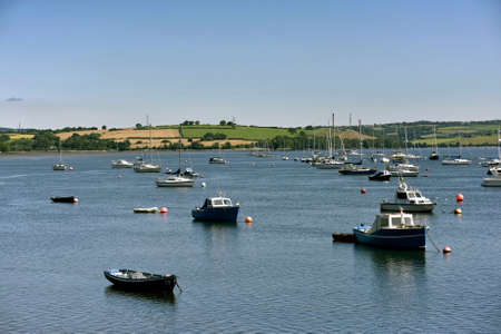 Yachts and fishing boats lies peacefully at anchor in a sheltered bay located at Saltash Cornwall UK