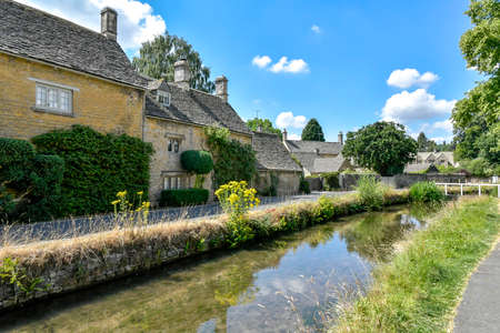 LOWER SLAUGHTER, THE COTSWOLDS, GLOUCESTERSHIRE, ENGLAND - JULY 14 th 2018: Cotswold stone cottages beside the River Eye in summer Banque d'images - 108088337