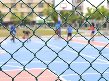 Seamless chain link fence with basketball court background  Stock Photo