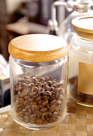 drywood:  Coffee beans in the glass bottle closeup at shop Stock Photo