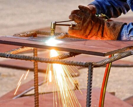 Oxygen and acetylene torch cutting steel with sparks