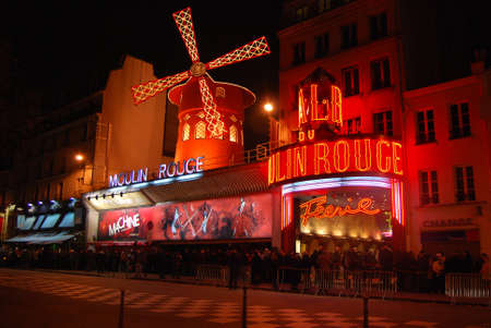 crowd tail: Night view of Moulin Rouge in Montmartre district, a well-known cabaret built in 1889 and one of the most famous touristic attractions